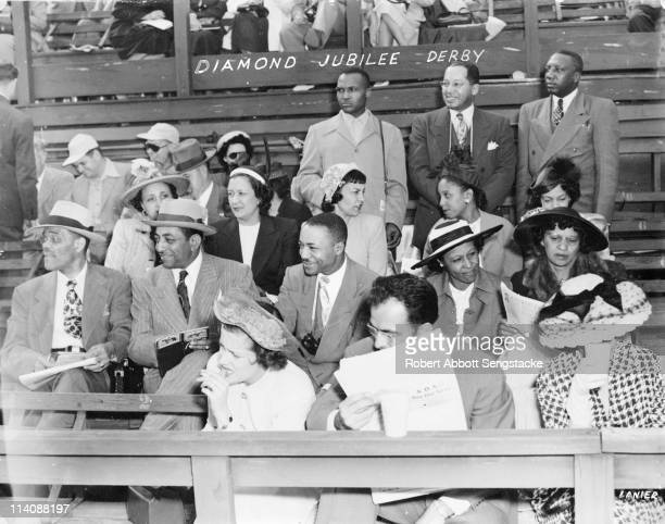 John H Sengstacke with friends and family enjoys the racing action while seated in the grandstand during the Kentucky Derby's Diamond Jubilee...