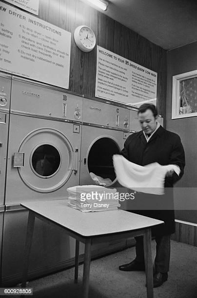 John Hanson folds his laundry at the launderette, UK, 18th February 1970.