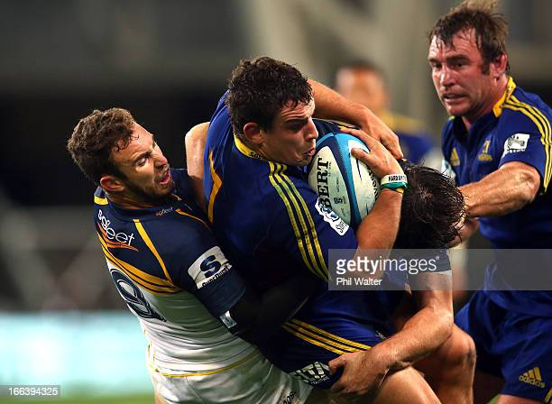 John Hardie of the Highlanders is tackled by Nic White of the Brumbies during the round nine Super Rugby match between the Highlanders and the...