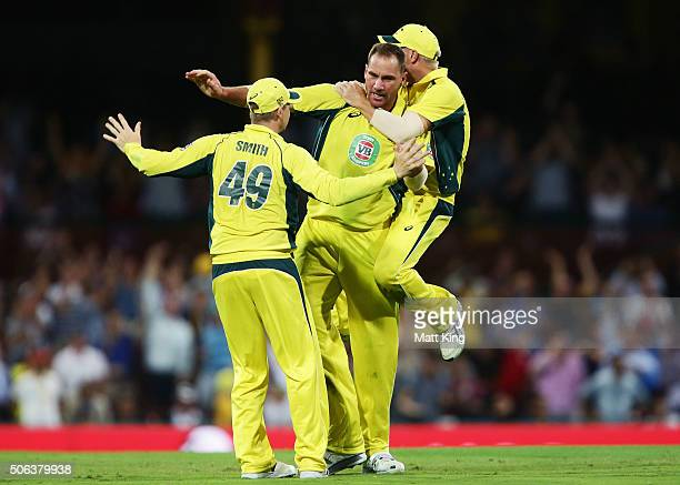 John Hastings of Australia celebrates with Steve Smith and David Warner after taking the wicket of Rohit Sharma of India during game five of the...
