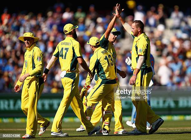 John Hastings of Australia celebrates with teammates the wicket of Virat Kohli of India during game three of the One Day International Series between...