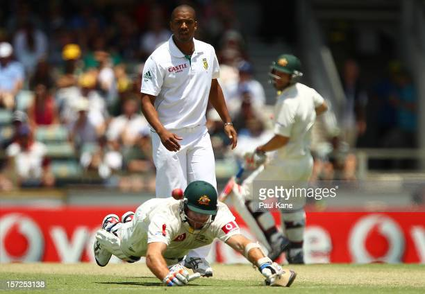 John Hastings of Australia dives to make his ground from a throw by Dean Elgar of South Africa as Vernon Philander looks on during day two of the...
