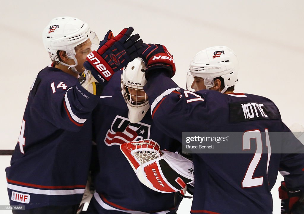 John Hayden #14, Brendan Burke #31 and Tyler Motte #21 of USA Blue celebrate their 2-1 victory over Team Finland during the 2014 USA Hockey Junior Evaluation Camp at the Lake Placid Olympic Center on August 3, 2014 in Lake Placid, New York.