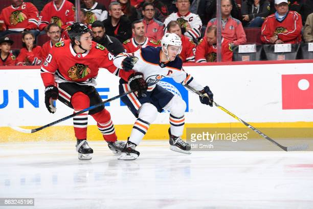 John Hayden of the Chicago Blackhawks and Connor McDavid of the Edmonton Oilers skate in the second period at the United Center on October 19 2017 in...