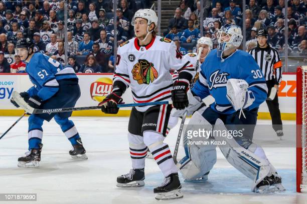 John Hayden of the Chicago Blackhawks and goaltender Laurent Brossoit of the Winnipeg Jets keep an eye at the point during first period action at the...