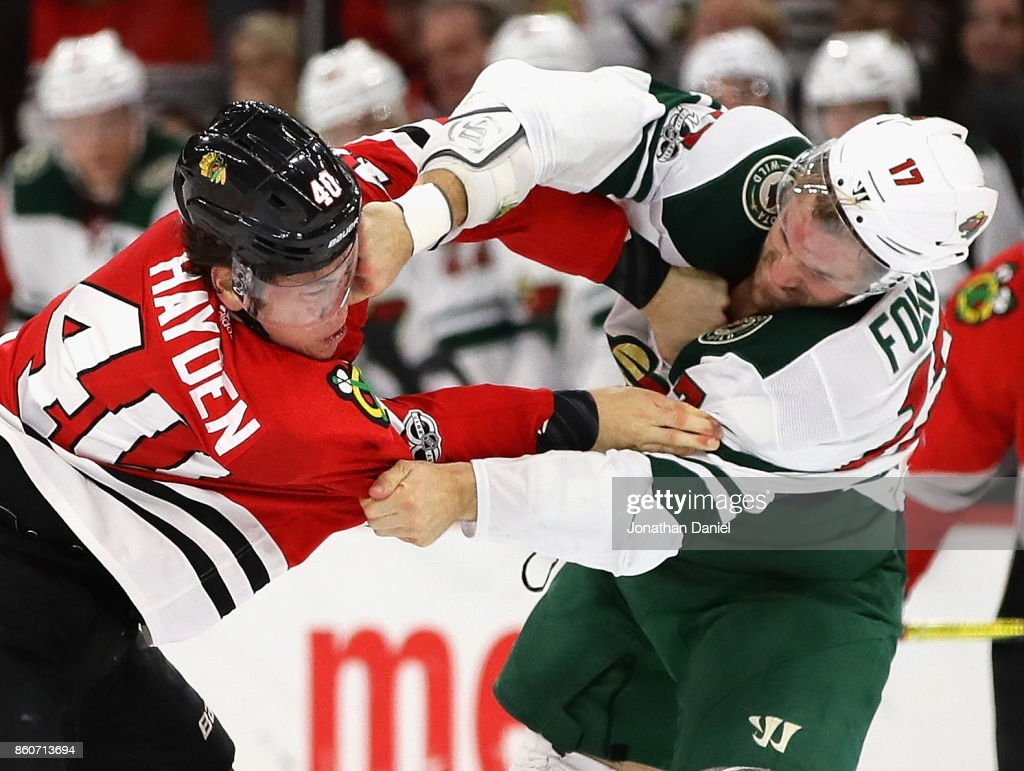 John Hayden #40 of the Chicago Blackhawks and Marcus Foligno #17 of the Minnesota Wild fight in the second period at the United Center on October 12, 2017 in Chicago, Illinois.