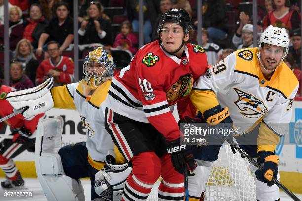 John Hayden of the Chicago Blackhawks and Roman Josi of the Nashville Predators watch for the puck next to goalie Pekka Rinne in the third period at...