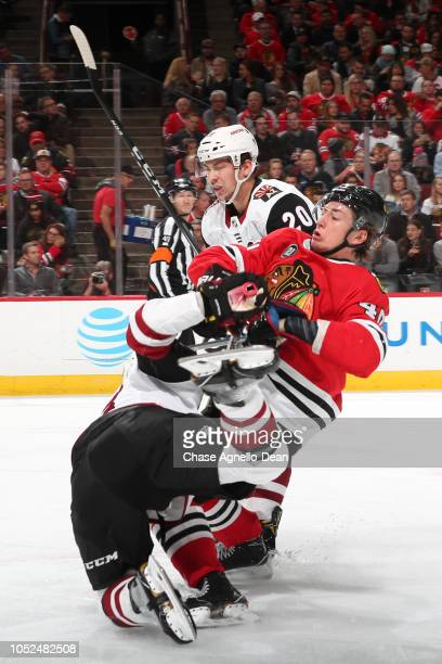 John Hayden of the Chicago Blackhawks gets physical with the Arizona Coyotes including Dylan Strome in the second period at the United Center on...
