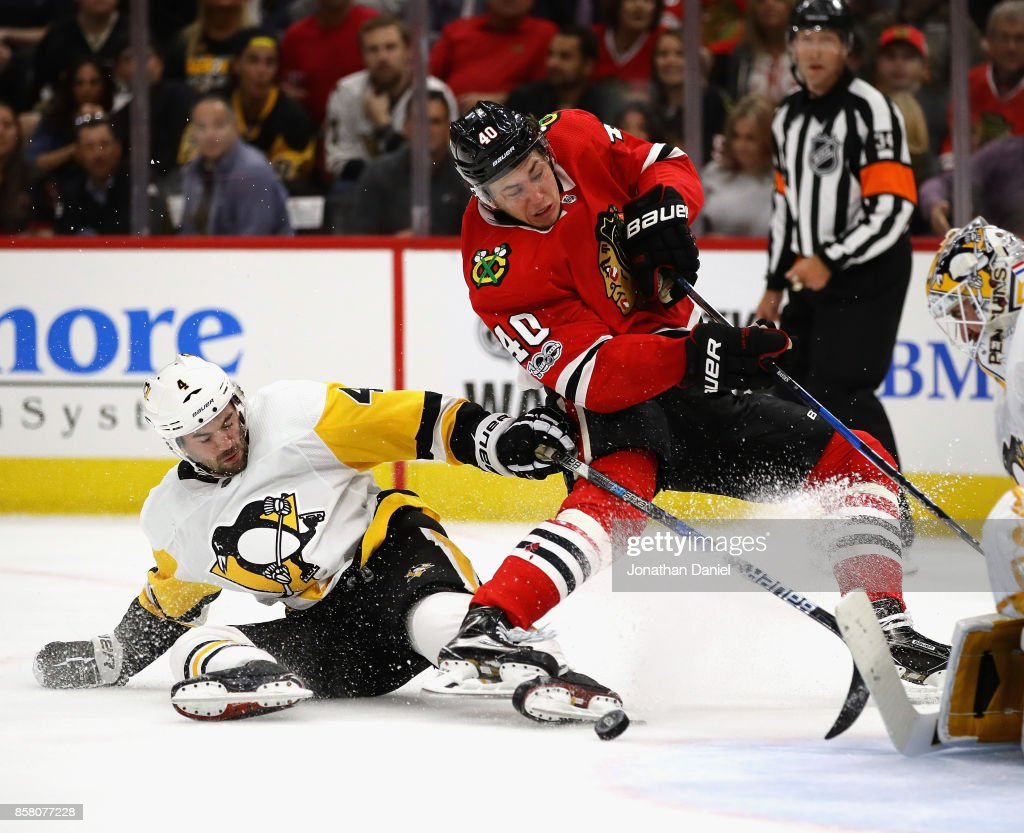John Hayden #40 of the Chicago Blackhawks is tripped while shooting by Justin Schultz #4 of the Pittsburgh Penguins during the season opening game at the United Center on October 5, 2017 in Chicago, Illinois.