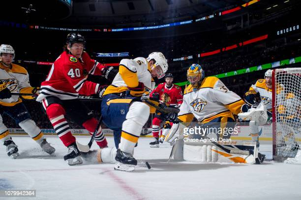 John Hayden of the Chicago Blackhawks pushes into Dan Hamhuis of the Nashville Predators as they chase the puck next to goalie Pekka Rinne at the...