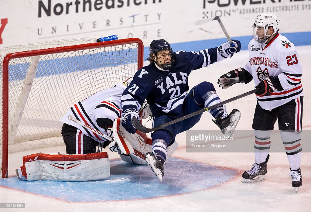 John Hayden #21 of the Yale Bulldogs trips in the goal crease and into Derick Roy #1 of the Northeastern Huskies as Colton Saucerman #23 watches during NCAA hockey at Matthews Arena on January 6, 2015 in Boston, Massachusetts.