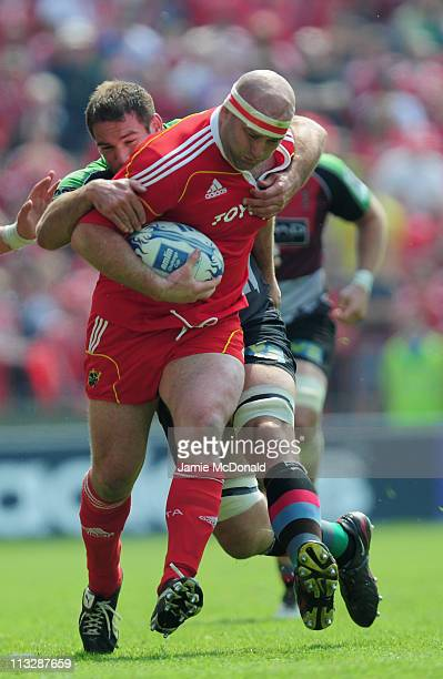 John Hayes of Munster is tackled by Ollie Kohn of Harlequins during the Amlin Cup semi-final match between Munster and Harlequins at Thomond Park on...