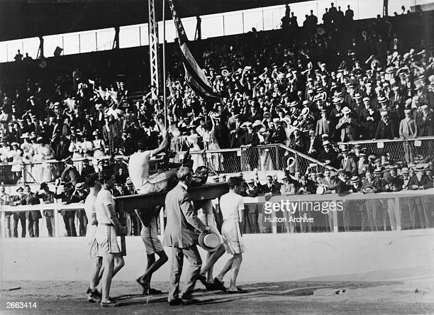 John Hayes of the USA is carried by team-mates on a table with the trophy for winning the Marathon at the 1908 London Olympics.