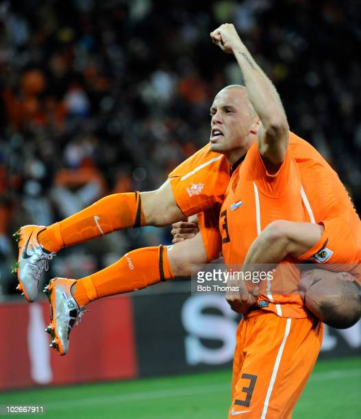John Heitinga lifts up teammate Wesley Sneijder of the Netherlands as they celebrate victory and progressing to the final after the 2010 FIFA World...