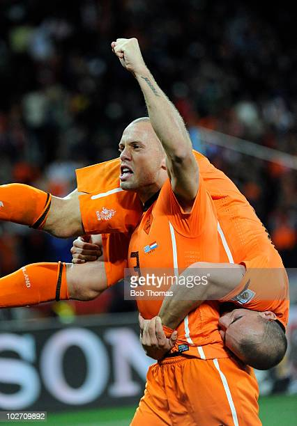 John Heitinga lifts up teammate Wesley Sneijder of the Netherlands as they celebrate victory and progress to the final after the 2010 FIFA World Cup...