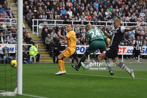 John Heitinga of Everton deflects the ball past goalkeeper Tim Howard to score an own goal during the Barclays Premier League match between Newcastle...