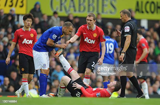 John Heitinga of Everton helps Wayne Rooney of Manchester United with and injury during the Barclays Premier League match between Everton and...