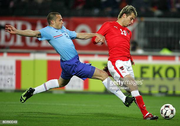 John Heitinga of the Netherlands and Andreas Ivanschitz of Austria fight for the ball during the international friendly match between Austria and...