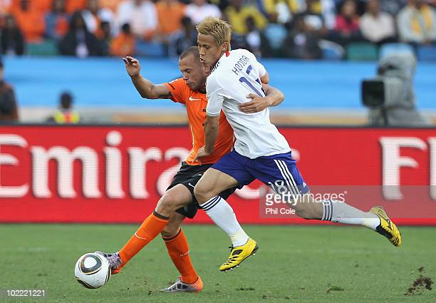 John Heitinga of the Netherlands and Keisuke Honda of Japan tussle for the ball during the 2010 FIFA World Cup South Africa Group E match between...