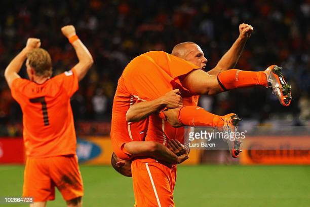 John Heitinga of the Netherlands carries Wesley Sneijder as they celebrate victory and progress to the final during the 2010 FIFA World Cup South...