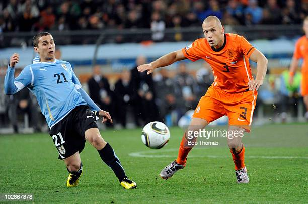 John Heitinga of the Netherlands handles the ball against Sebastian Fernandez of Uruguay during the 2010 FIFA World Cup South Africa Semi Final match...