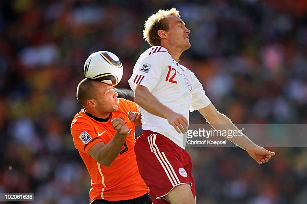 John Heitinga of the Netherlands heads the ball under pressure from Thomas Kahlenberg of Denmark during the 2010 FIFA World Cup Group E match between...