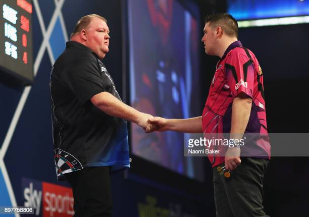 John Henderson of Scotland shakes hands with Daryl Gurney of Northern Ireland after winning the second round match on day ten of the 2018 William...