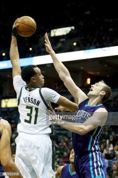 John Henson of the Milwaukee Bucks attempts a shot while being guarded by Cody Zeller of the Charlotte Hornets in the second quarter at BMO Harris...