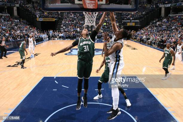 John Henson of the Milwaukee Bucks attempts to block the shot by Deyonta Davis of the Memphis Grizzlies during the game on March 12 2018 at...