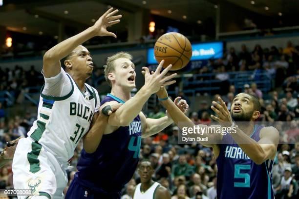 John Henson of the Milwaukee Bucks battles for a rebound against Cody Zeller and Nicolas Batum of the Charlotte Hornets in the second quarter at BMO...