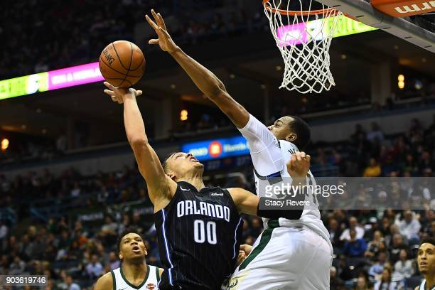John Henson of the Milwaukee Bucks blocks a shot by Aaron Gordon of the Orlando Magic during the second half of a game at the Bradley Center on...