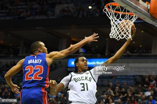 John Henson of the Milwaukee Bucks drives to the basket against Avery Bradley of the Detroit Pistons during the first half of a game at the Bradley...