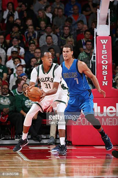 John Henson of the Milwaukee Bucks posts up against Dwight Powell of the Dallas Mavericks during a preseason game on October 8 2016 at the Kohl...