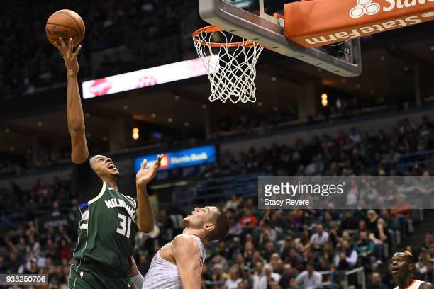 John Henson of the Milwaukee Bucks shoots over Mike Muscala of the Atlanta Hawks during the second half of a game at the Bradley Center on March 17...