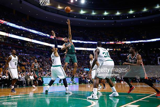 John Henson of the Milwaukee Bucks takes a shot over Jared Sullinger of the Boston Celtics in the second half during the game at TD Garden on...