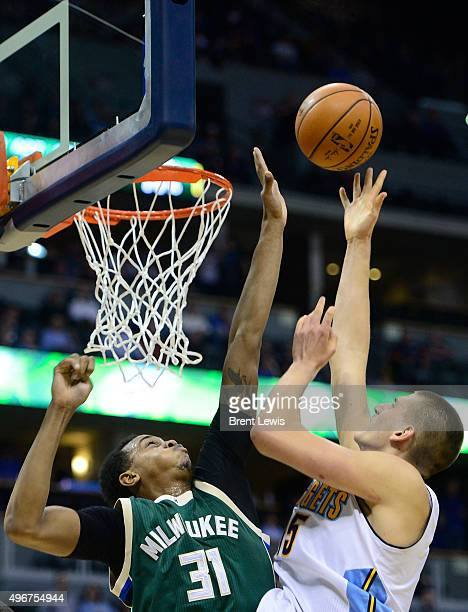 John Henson of the Milwaukee Bucks tries to block the shot of Nikola Jokic of the Denver Nuggets during the second quarter at the Pepsi Center on...