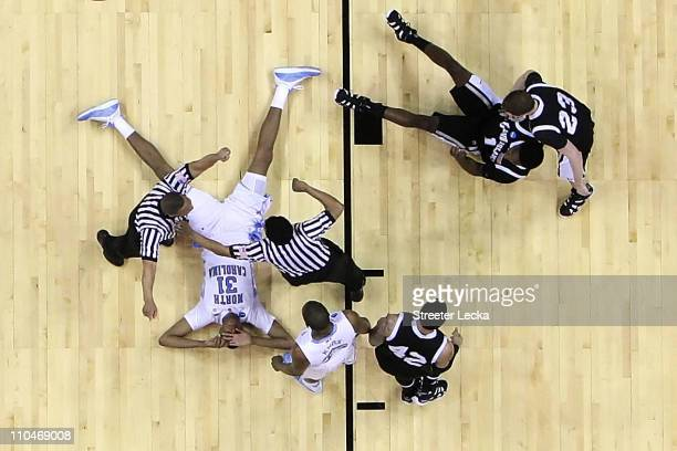 John Henson of the North Carolina Tar Heels and Jamal Olasewere of the Long Island Blackbirds lay on the floor after a collision during the second...