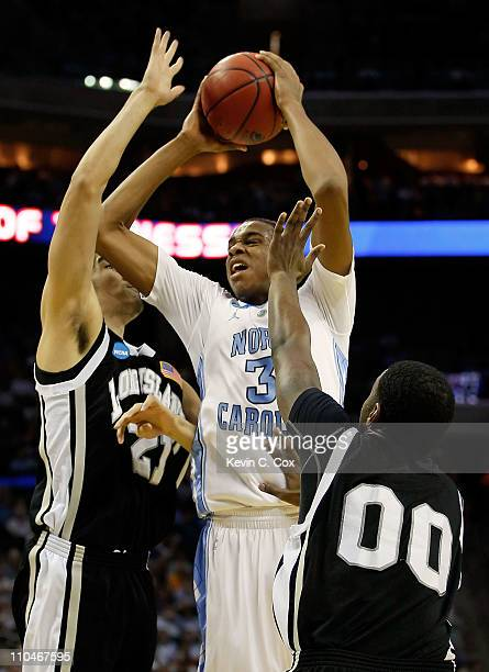 John Henson of the North Carolina Tar Heels goes up for a shot between Arnold Mayorga and Kyle Johnson of the Long Island Blackbirds in the first...