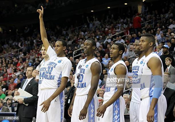 John Henson of the North Carolina Tar Heels points to the sky on bench to celebrate the defeat of the Marquette Golden Eagles during the east...
