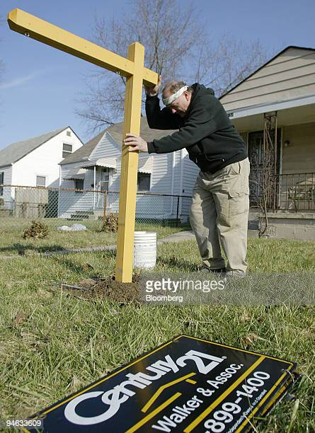 John Hertlein, owner of Real Estate Signs and Services, hangs a Century 21 for sale sign in front of a new listing in Columbus, Ohio Monday, Dec. 18,...