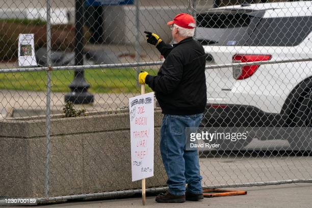 John Hess, a Donald Trump supporter, holds a sign while protesting at the Washington State Capitol on January 20, 2021 in Olympia, Washington. One...