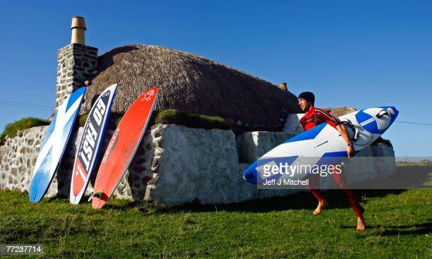 John Hibbard, the only British competitor in the Corona Extra PWA World Cup,runs past a thatched cottage beside Balevullin beach on the Hebridean...