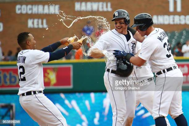 John Hicks of the Detroit Tigers celebrates his game winning RBI bunt in the 12th inning to beat the Tampa Bay Rays 32 with Leonys Martin and James...