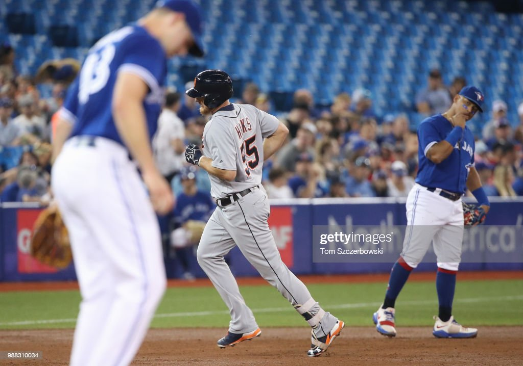 John Hicks #55 of the Detroit Tigers circles the bases after hitting a solo home run in the second inning during MLB game action as Sam Gaviglio #43 of the Toronto Blue Jays reacts at Rogers Centre on June 30, 2018 in Toronto, Canada.