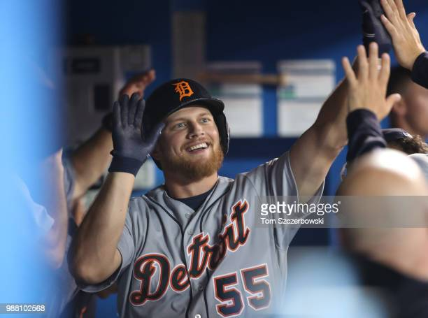 John Hicks of the Detroit Tigers is congratulated by teammates in the dugout after hitting a solo home run in the second inning during MLB game...