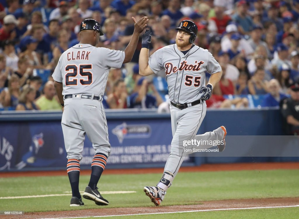 John Hicks #55 of the Detroit Tigers is congratulated by third base coach Dave Clark #25 after hitting a solo home run in the second inning during MLB game action against the Toronto Blue Jays at Rogers Centre on June 30, 2018 in Toronto, Canada.