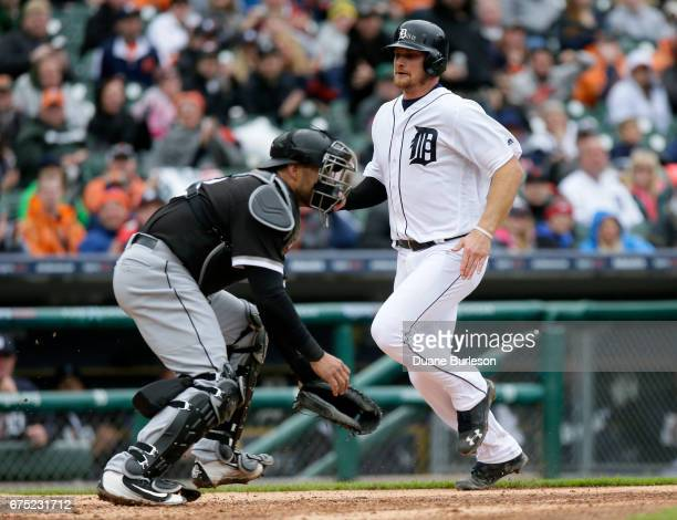 John Hicks of the Detroit Tigers scores against catcher Geovany Soto of the Chicago White Sox on a double by Jose Iglesias of the Detroit Tigers...
