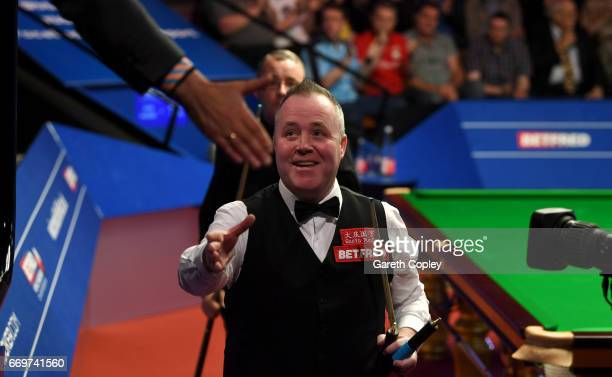 John Higgins celebrates after beating Martin Gould during their first round match of the World Snooker Championship at Crucible Theatre on April 18...