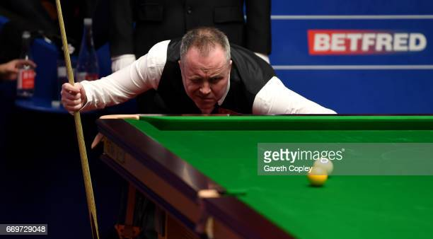 John Higgins lines up a shot against Martin Gould during their first round match of the World Snooker Championship at Crucible Theatre on April 18...