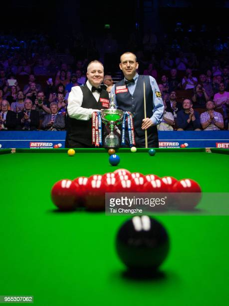 John Higgins of Scotland and Mark Williams of Wales pose with the trophy before the final match on day sixteen of the World Snooker Championship at...